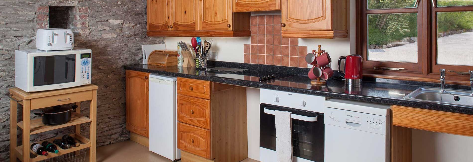 Buzzard Watch Kitchen showing clear underspace for the hob and sink and a worktop level combination microwave. The hob can be lowered for easier access.